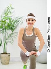 Smiling slim woman making stretching exercises