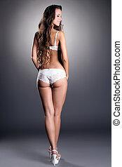 Smiling slim woman posing in white lingerie