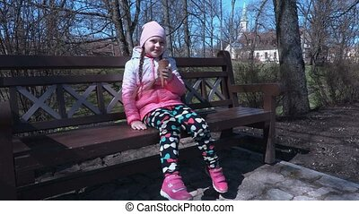 Smiling small girl eating ice cream and show thumb up