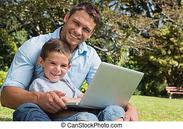 Smiling son and dad with a laptop on their knees in the park