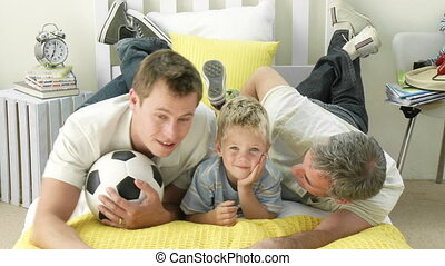 Smiling son, father and grandfather lying on the bed