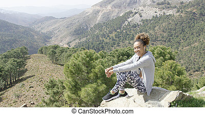 Smiling sportive woman on rock