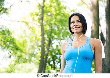 Smiling sports woman in headphones outdoors. looking away