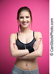 Smiling sports woman standing with arms folded over pink background