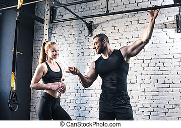 smiling sportsman gesturing and talking to attractive sportswoman in sports center