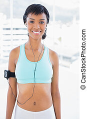Smiling sportswoman listening to music