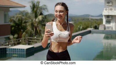 Smiling sportswoman listening to music near swimming pool