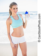 Smiling sporty blonde in sportswear holding flask - Smiling...