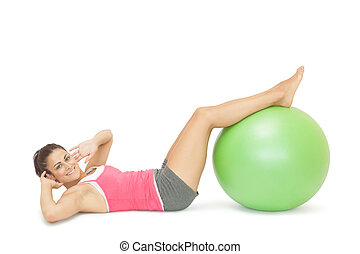 Smiling sporty brunette doing sit ups with exercise ball on ...