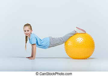 smiling sporty girl exercising with fitness ball on white
