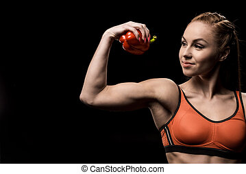 smiling sporty girl holding bell pepper solated on black