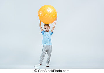 smiling sporty girl holding fitness ball on white
