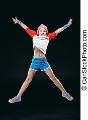 Smiling sporty girl jumping isolated on black, activities for children concept