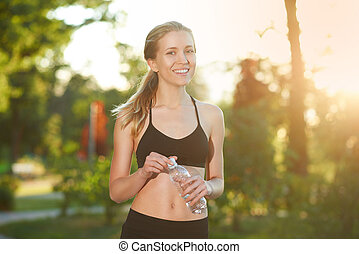 Smiling sporty girl keeping bottle with water.