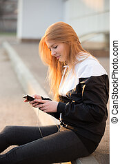 Smiling sporty girl with smartphone