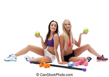 Smiling sporty models posing with gymnastic balls