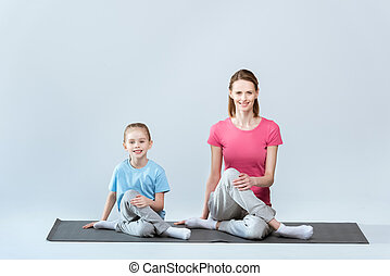 Smiling sporty mother and daughter practicing yoga, gomukhasana pose on white