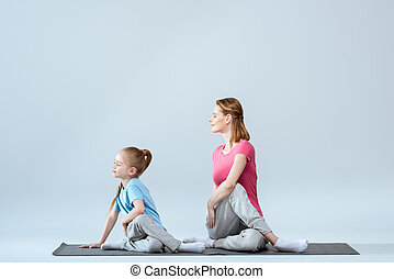 Smiling sporty mother and daughter practicing yoga Gomukhasana pose on white