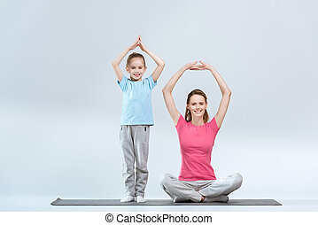 smiling sporty mother and daughter practicing yoga together on white
