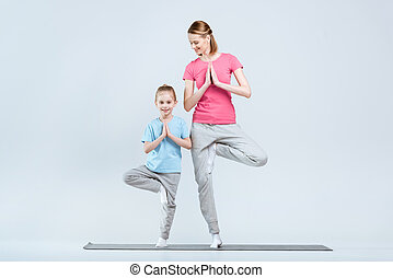 Smiling sporty mother and daughter practicing yoga together, Vrikshasana yoga pose or tree pose on white