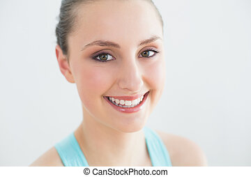 Smiling sporty woman against wall