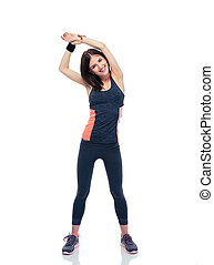 Smiling sporty woman doing stretching exercise