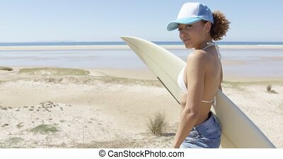 Smiling sporty woman embracing surfboard - Cheerful young ...