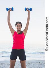 Smiling sporty woman holding dumbbells