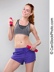 Smiling sporty woman holding weights