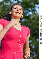 Smiling sporty woman jogging in a park