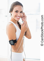 Smiling sporty woman listening to music