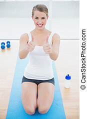 Smiling sporty woman on her knees giving thumbs up to camera