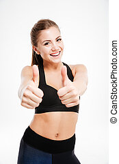 Smiling sporty woman showing thumb up sign over white ...