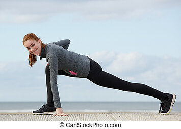 Smiling sporty woman stretching legs