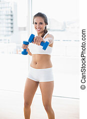 Smiling sporty woman using dumbbells