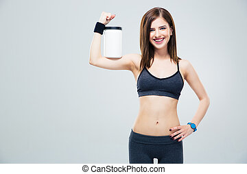 Smiling sporty woman with jar of protein on hand over gray...