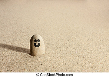 Smiling stone sticking out of the sand