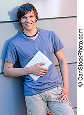 Smiling student boy leaning against modern wall