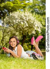 Smiling student girl lying in summer park