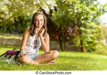 Smiling student girl sitting grass summer park