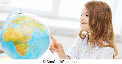 smiling student girl with globe at school - education and...