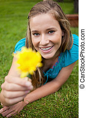 Smiling student holding a beautiful yellow flower while looking straight at the camera