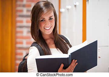 Smiling student holding a book in a corridor