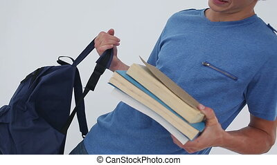 Smiling student holding books and his backpack against a...