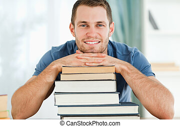 Smiling student leaning on his books