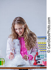 Smiling student looking at reaction of reagents