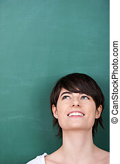 Smiling student looks up in front of a blackboard