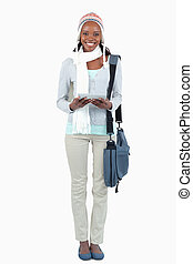 Smiling student with scarf, hat and touchpad against a white...