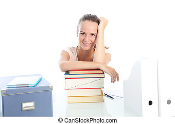 Smiling female student sitting at her desk relaxing with her arms on top of a pile of textbooks on a white background