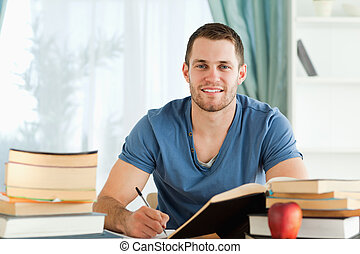 Smiling student working on his book report